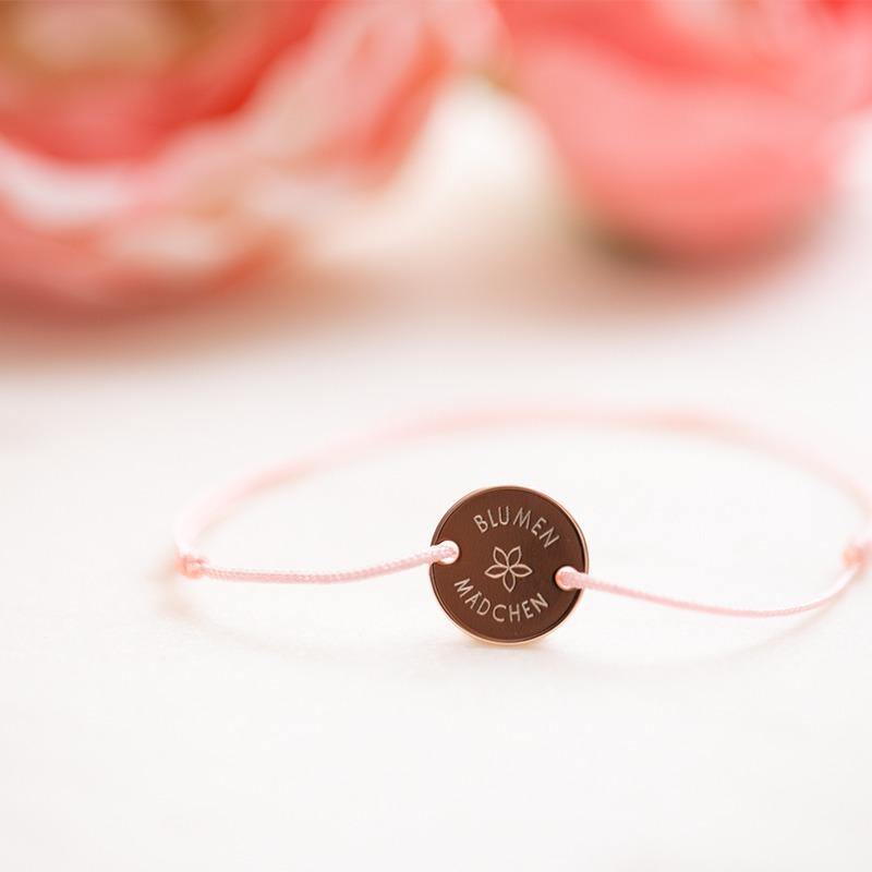 Nylonband mit Schiebeschließe und Gravurplatte auf der das Wort Blumenmädchen im Rundbogen graviert ist. Mittig eine Blume