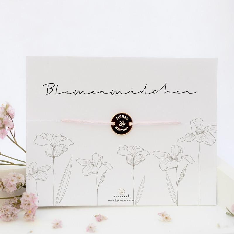 Armband, das aus einem runden Gravurplättchen besteht, in dem das Wort Blumenmädchen und eine Blume graviert sind, zusammengehalten von einer Nylonkordel. Auf dem beigefügten Kärtchen steht auch Blumenmädchen.