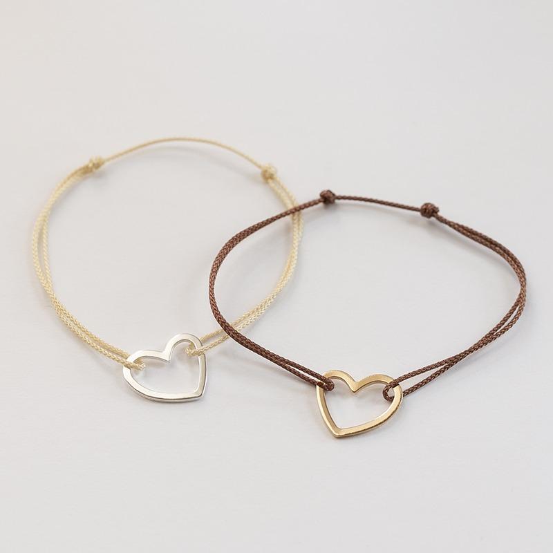 Vergoldetes oder versilbertes Herzarmband. Es ist ein irregulär geschnittenes Herz, das von einer Nylonkordel gehalten wird