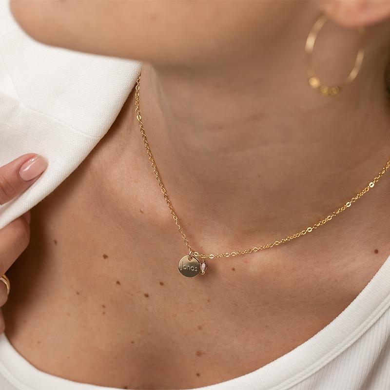 Zarte Gravurkette, an der ein personalisiertes Plättchen hängt neben einem Kristall