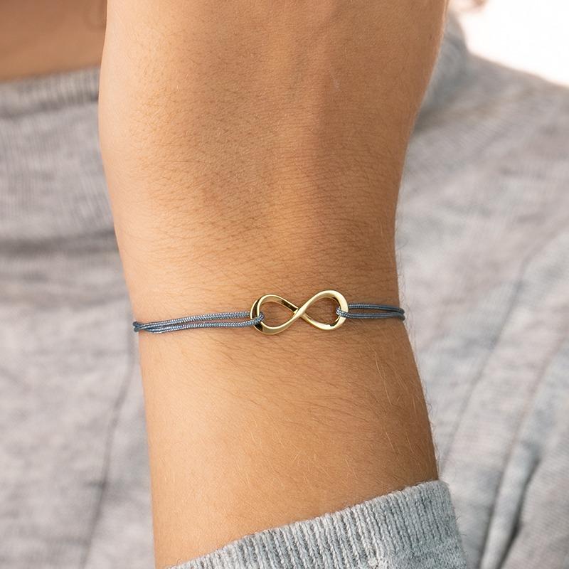 Armband mit einem Anhänger als Unendlichkeits Symbol das von einem Nylonband gehalten wird