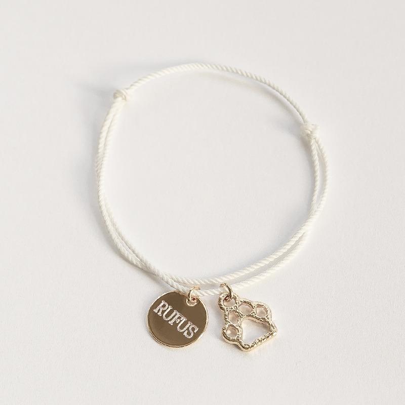 Armband bestehend aus einer geknoteten Seidenkordel, die Enden lassen sich schieben, dran hängt ein Pfote Anhänger und ein rundes Gravurplättchen in 12mm