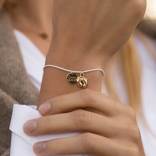 Armband aus einer Seidenkordel, an dem Babyfüße als Anhänger und ein 10mm Gravurplättchen baumelt