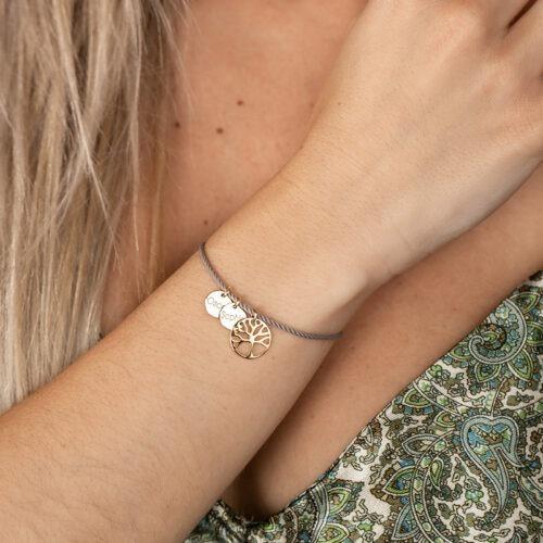 Armband mit Seidenkordel an der ein Lebensbaum hängt und Gravurplatten