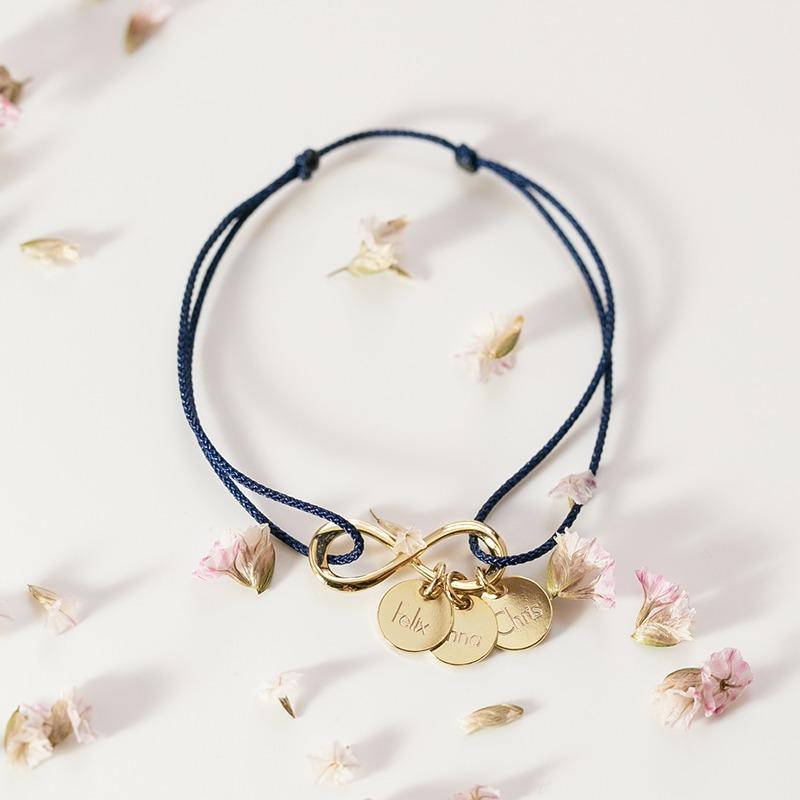 Personalisiertes Armband mit Infinity Anhänger an dem Gravuranhänger baumeln