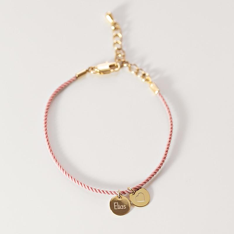 Armband mit einer gedrehten Seidenkordel an der zwei kleine runde Gravurplättchen hängen, die wir personalisieren