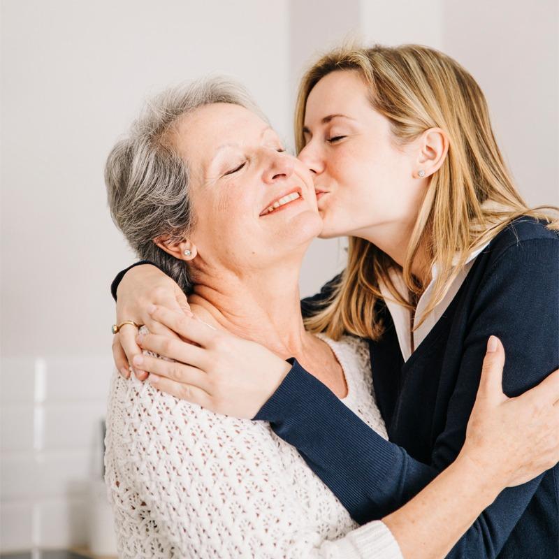 Mutter und Tochter umarmen sich glücklich zum Muttertag