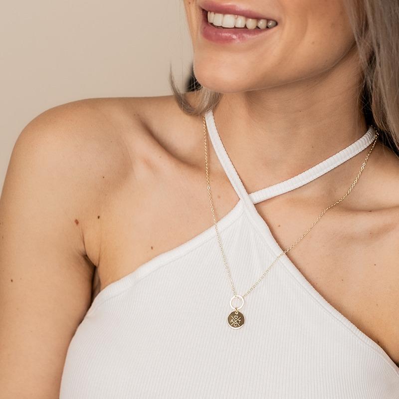 Goldene Halskette an der ein Ring baumelt und an diesem wiederum ein rundes Gravurplättchen