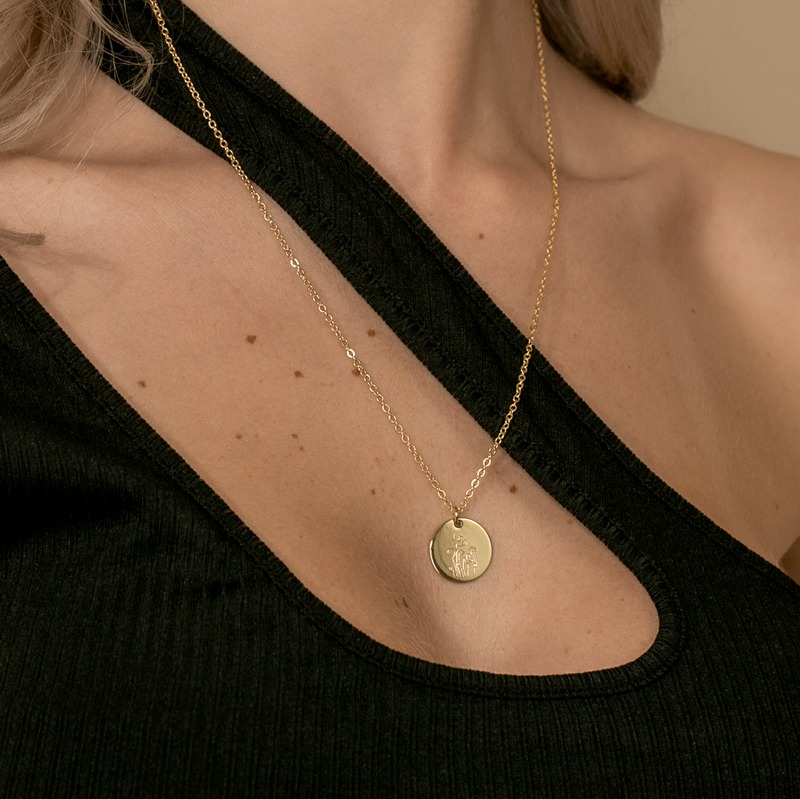 Halskette mit rundem Anhänger auf dem die Geburtsblume graviert ist